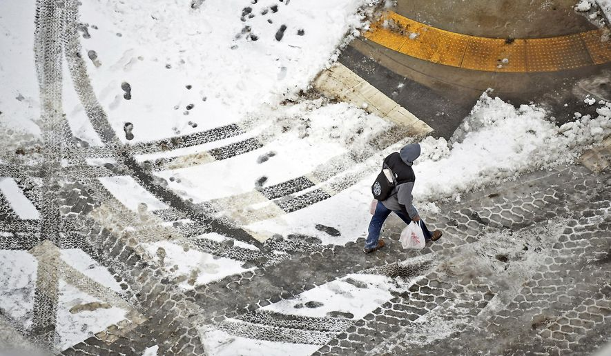 A pedestrian walks across the street in downtown Scranton, Pa., on Sunday, Jan. 20, 2019. A major winter storm brought some of the coldest temperatures of the season and covered a large swath of the country in snow as it wreaked havoc on air travel and caused slick road conditions throughout New England Sunday. (Butch Comegys/The Times-Tribune via AP)