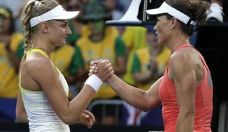 Ukraine's Dayana Yastremska, left, is congratulated by Australia's Samantha Stosur after winning their first round match at the Australian Open tennis championships in Melbourne, Australia, Tuesday, Jan. 15, 2019. (AP Photo/Aaron Favila)