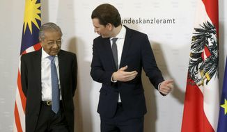 Austrian Chancellor Sebastian Kurz, right, welcomes Malaysia's Prime Minister Mahathir Mohamad, left, for a meeting at the federal chancellery in Vienna, Austria, Monday, Jan. 21, 2019. (AP Photo/Ronald Zak)