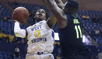 West Virginia guard Trey Doomes (0) shoots while defended by Baylor guard Mark Vital (11) during the second half of an NCAA college basketball game Monday, Jan. 21, 2019, in Morgantown, W.Va. (AP Photo/Raymond Thompson)