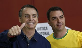 FILE - In this Oct. 7, 2018 file photo, then-presidential frontrunner Jair Bolsonaro, left, accompanied by his son Flavio Bolsonaro, arrives to vote in the general election in Rio de Janeiro, Brazil. Flavio, the son of current President Jair Bolsonaro, is fending off suspicions of financial irregularities that are starting to cast a shadow over the new administration.  (AP Photo/Silvia Izquierdo, File)