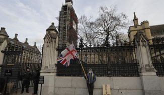 A lone demonstrator stands by an entrance to Britain's parliament in London, Friday, Jan. 18, 2019. Talks to end Britain's Brexit stalemate appeared deadlocked Friday, with neither Prime Minister Theresa May nor the main opposition leader shifting from their entrenched positions. (AP Photo/Kirsty Wigglesworth)