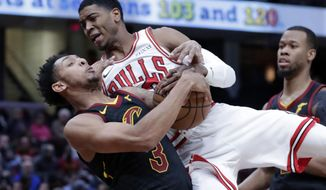 Cleveland Cavaliers' Cameron Payne, left, and Chicago Bulls' Shaquille Harrison battle for the ball in the first half of an NBA basketball game, Monday, Jan. 21, 2019, in Cleveland. (AP Photo/Tony Dejak)