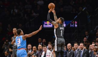 Brooklyn Nets guard D'Angelo Russell (1) shoots over Sacramento Kings guard Yogi Ferrell (3) during the first half of an NBA Basketball game, Monday, Jan. 21, 2019, in New York. (AP Photo/Howard Simmons)