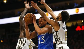 Orlando Magic guard Isaiah Briscoe (13) is defended by Atlanta Hawks center Dewayne Dedmon (14) and guard Tyler Dorsey (2) in the second half of an NBA basketball game on Monday, Jan. 21, 2019, in Atlanta. (AP Photo/Todd Kirkland)