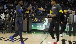 Milwaukee Bucks' Giannis Antetokounmpo, right, and Dallas Mavericks' Kostas Antetokounmpo, left, greet at midcourt before an NBA basketball game Monday, Jan. 21, 2019, in Milwaukee. (AP Photo/Aaron Gash)
