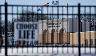 Flags fly over the Covington Catholic High School stadium in Park Kills, Ky., Sunday, Jan 20, 2019. A diocese in Kentucky has apologized after videos emerged showing students from the Catholic boys' high school mocking Native Americans outside the Lincoln Memorial on Friday after a rally in Washington. (AP Photo/Bryan Woolston)