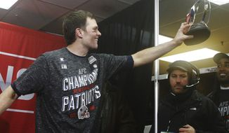 New England Patriots quarterback Tom Brady hands off the championship trophy to his teammates after the AFC Championship NFL football game against the Kansas City Chiefs, Sunday, Jan. 20, 2019, in Kansas City, Mo. (AP Photo/Charlie Riedel)