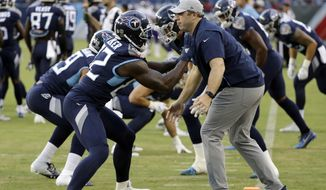 """File-This Aug. 30, 2018, file photo shows Tennessee Titans tight ends coach Arthur Smith, right, helping tight end Delanie Walker (82) warm up before a preseason NFL football game in Nashville, Tenn. Mike Vrabel has stayed inside the Tennessee Titans' organization for his new offensive coordinator, promoting tight ends assistant Smith to the job vacated when Matt LaFleur left for the Green Bay Packers' head coaching job.Vrabel announced the promotion Monday, jan. 21, 2019, saying he's excited for both Smith and the Titans to promote a """"deserving coach.""""(AP Photo/James Kenney, File)"""
