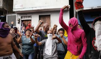 Residents protest in support of a mutiny by a national guard unit and against Venezuelan President Nicolas Maduro in the Cotiza neighborhood of Caracas, Venezuela, Monday, Jan. 21, 2019. Security forces have fired tear gas against protesters in a poor neighborhood near the presidential palace after an apparent uprising by a national guard unit. (AP Photo/Ariana Cubilos)