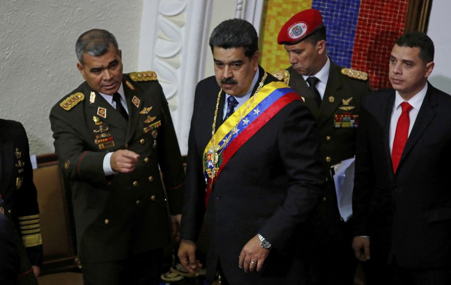 Venezuela's President Nicolas Maduro, center, stands with his Defense Minister Vladimir Padrino Lopez before giving his annual address to the nation to members of the Constitutional Assembly inside the National Assembly in Caracas, Venezuela, Monday, Jan. 14, 2019. (AP Photo/Ariana Cubillos)