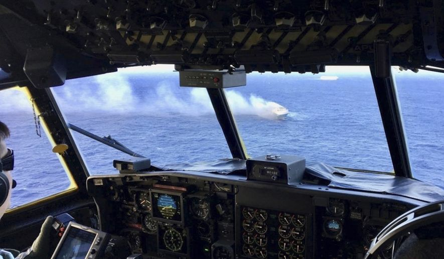 FILE - In this Dec. 31, 2018 file photo provided by the U.S. Coast Guard, a Coast Guard HC-130 Hercules aircrew flies over the 650-foot Sincerity Ace on fire 1,800 nautical miles northwest of Oahu in the Pacific Ocean. A tugboat has reached the ship abandoned by crew members after it caught fire while transporting automobiles from Japan to Hawaii last week. The Sincerity Ace had 21 crew members on board when the fire started last week. The crew members abandoned the burning vessel, which stretches 650 feet (198 meters). Ships in the area rescued 16. Four were listed as unresponsive in the water. A company spokesman said tugboat crew members who arrived Monday, Jan. 8, 2019, will first try to find the remaining five crew members. (U.S. Coast Guard via AP)