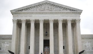 In this Oct. 9, 2018 photo, police office guards the main entrance to the Supreme Court in Washington.  The Supreme Court is taking up its first gun rights case in nine years, a challenge to New York City's prohibition on carrying a licensed, locked and unloaded handgun outside the city limits. The court's decision Tuesday to take on the appeal filed by three New York residents and New York's National Rifle Association affiliate could signal a revived interest in gun rights by a more conservative court. The case won't be argued until October.(AP Photo/Pablo Martinez Monsivais)