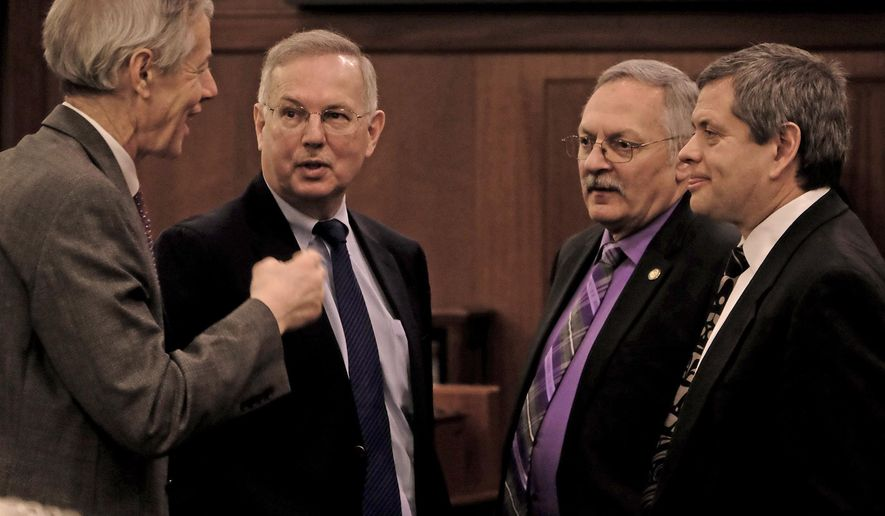 Members of the Alaska state House of Representatives, Matt Claman, from left, of Anchorage, Bryce Edgmon of Dillingham, Dave Talerico of Healy and Chris Tuck of Anchorage speak together during the floor session at the Capitol Tuesday, Jan. 22, 2019, in Juneau, Alaska. Even though the House does not have an organized majority, members adjusted rules to accept Gov. Mike Dunleavy's request to hold the State of the State address Tuesday evening. (Klas Stolpe/The Daily Sitka Sentinel via AP)