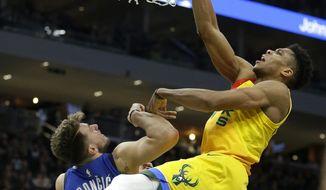 Milwaukee Bucks' Giannis Antetokounmpo dunks against Dallas Mavericks' Luka Doncic during the second half of an NBA basketball game Monday, Jan. 21, 2019, in Milwaukee. (AP Photo/Aaron Gash)