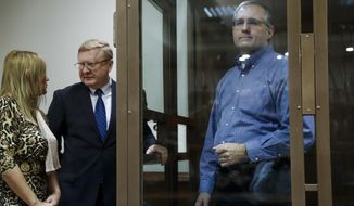 Paul Whelan, a former U.S. Marine, who was arrested in Moscow at the end of last year, right, looks through a cage's glass as his lawyers talk to each other in a court room in Moscow, Russia, Tuesday, Jan. 22, 2019. The lawyer for Paul Whelan who is being held in Moscow on suspicion of spying, said Tuesday that classified Russian materials were found on him when he was arrested. (AP Photo/Pavel Golovkin)