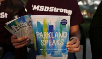 """In this Wednesday, Jan. 16, 2019, photo, Leni Steinhardt, 16, reads from a new book called """"Parkland Speaks: Survivors from Marjory Stoneman Douglas Share Their Stories,"""" during an interview with The Associated Press, in Parkland, Fla. (AP Photo/Brynn Anderson)"""