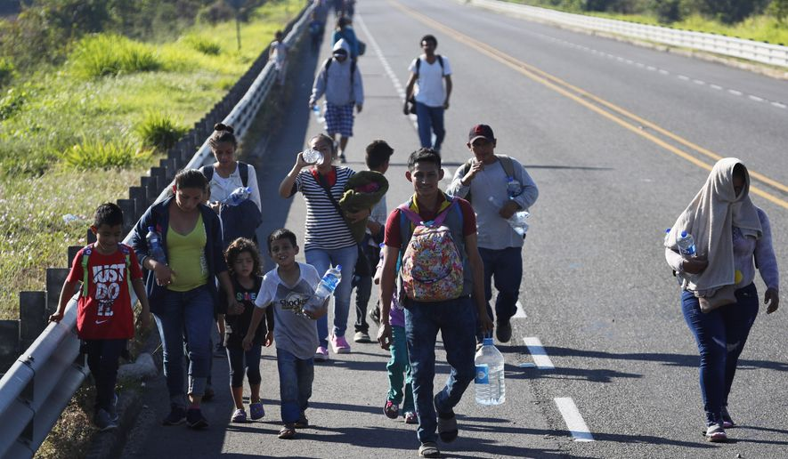 Honduras migrants, part of the caravan hoping to reach the U.S. border, walk on a road in Tapachula, Chiapas State, Mexico, Friday, Jan. 18,2019. Hundreds of Central American migrants are walking and hitchhiking through the region as part of a new caravan of migrants hoping to reach the United States. (AP Photo/Marco Ugarte)