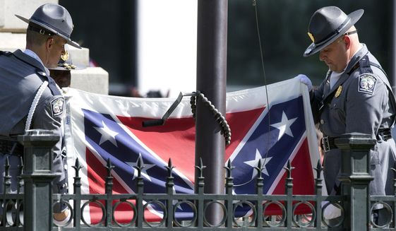 In this July 10, 2015, photo, members of an honor guard from the South Carolina Highway patrol lower the Confederate battle flag as it is removed from the Capitol grounds in Columbia, S.C. Confederate Relic Room Executive Director Allen Roberson said Tuesday, Jan. 22, 2019, museum staff put the flag into a $1,400 protective case on Nov. 26, ending a more than three-year saga. (AP Photo/John Bazemore) **FILE**
