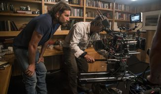 "CORRECTS CATEGORY - This image released by Warner Bros. Pictures shows director/co-writer/producer Bradley Cooper, left, and camera operator Scott Sakamoto on the set of ""A Star is Born."" On Tuesday, Jan. 22, 2019, Cooper was not nominated for an Oscar for best director for his work on the film. He was nominated for best actor for his role in the film. The 91st Academy Awards will be held on Feb. 24.  (Clay Enos/Warner Bros. via AP)"