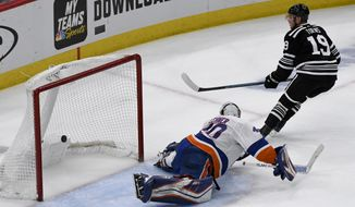 Chicago Blackhawks center Jonathan Toews (19) scores a shootout goal past New York Islanders goaltender Robin Lehner (40) during an NHL hockey game on Tuesday Jan. 22, 2019, in Chicago. The Chicago Blackhawks won 3-2. (AP Photo/Matt Marton)
