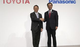 FILE - In this Dec. 13, 2017, file photo, Toyota Motor Corporation President Akio Toyoda, left, and Panasonic Corporation President Kazuhiro Tsuga, right, pose for photographers after a joint press conference in Tokyo. Toyota Motor Corp. and Panasonic Corp. said in a joint statement Tuesday, Jan. 22, 2019, they are setting up a joint venture to research, manufacture and sell batteries for ecological autos, an increasingly lucrative sector amid concerns about global warming. (AP Photo/Eugene Hoshiko, File)