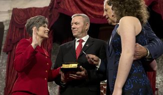 FILE - In this Jan. 6, 2015 file photo, Vice President Joe Biden administers the Senate oath to Sen. Joni Ernst R-Iowa, with her husband Gail Ernst and daughter Elizabeth, during a ceremonial re-enactment swearing-in ceremony in the Old Senate Chamber of Capitol Hill in Washington. Ernst says she turned down Donald Trump's request to run as his vice president in 2016 because of family concerns. Ernst made the claim in an affidavit in a divorce proceeding in October that was first reported by CityView, a Des Moines weekly newspaper. The filing was unsealed earlier this month after Ernst and her former husband of 25 years, Gail Ernst, settled their previously contentious divorce. (AP Photo/Jacquelyn Martin, File)