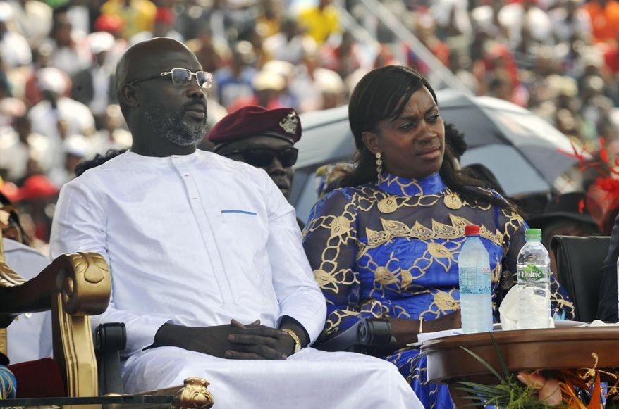 "FILE - In this Jan. 22, 2018, file photo, Liberia's new President George Weah, left and his wife, Clar Weah, right, sit during his inauguration ceremony in Monrovia Liberia. Star footballer-turned-politician George Weah marks a year as Liberia's president on Tuesday Jan. 22, 2019, as many in the impoverished country debate whether he has begun to deliver on dramatic campaign promises. FIFA's 1995 player of the year in his inaugural speech vowed to give the West African nation's young population hope through job creation and a war on corruption, saying ""Liberians will no longer be spectators in their own economy."" (AP Photo/Abbas Dulleh, File)"