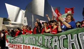 FILE - In this Dec. 15, 2018, file photo, United Teachers Los Angeles leaders are joined by thousands of teachers as they march past the Walt Disney Concert Hall downtown Los Angeles. The union representing striking teachers in Los Angeles says the strike will continue into its sixth school day on Tuesday, Jan. 22, 2019, regardless of the outcome of negotiations Monday. (AP Photo/Damian Dovarganes, File)