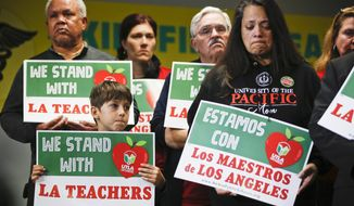 FILE - In this Jan. 13, 2019, file photo, student Leo Rittner Solomon, 6, front left, and parent Hilda Rodriguez Guzman, right, react as United Teachers Los Angeles president and teacher Alex Caputo-Pearl announces the nation's second-largest school district, Los Angeles Unified School District, was going on strike in Los Angeles. The union said Monday, Jan. 21, that teachers are due back at picket lines Tuesday morning even if an agreement is reached Monday, saying it takes time to mobilize a ratification vote of a deal. (AP Photo/Damian Dovarganes, File)