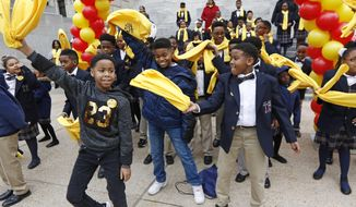 """Elementary school students dance """"the floss"""" as they participate in a school choice rally, part of the National School Choice Week, on the steps of the Capitol in Jackson, Miss., Tuesday, Jan. 22, 2019. Lawmakers, government officials, family members and students gathered to raise public awareness for the different K-12 education options available. (AP Photo/Rogelio V. Solis)"""