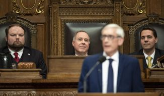 Wisconsin Assembly Speaker Robin Vos, center, watches as Wisconsin Gov. Tony Evers addresses a joint session of the Legislature in the Assembly chambers during the Governor's State of the State speech at the state Capitol Tuesday, Jan. 22, 2019, in Madison, Wis. Behind Evers is Assembly Speaker Pro Tempore Tyler August, left, R-Lake Geneva, and Senate President Roger Roth, R-Appleton. (AP Photo/Andy Manis)