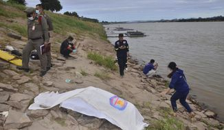 In this photo dated Thursday, Dec, 27, 2018, Thai rescuers cover a body on the shore of the Mekong River in Nakhon Phanom province northeast of Bangkok, Thailand.  DNA tests show that two bodies found washed up on the shore of Thailand's Mekong River are the corpses of anti-government activists, police said Tuesday, Jan. 22, 2019, in what are feared to be political killings. The two, known by the pseudonyms Puchana and Kasalong, were among three exiled activists who disappeared in December from homes in Laos, where they took shelter after fleeing Thailand. (AP Photo)