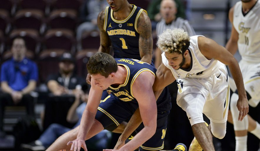 Michigan's Jon Teske, left, steals the ball from George Washington's Justin Mazzulla (0) in the second half of an NCAA college basketball game, Saturday, Nov. 17, 2018, in Uncasville, Conn. Michigan won 84-61. (AP Photo/Stephen Dunn) **FILE**