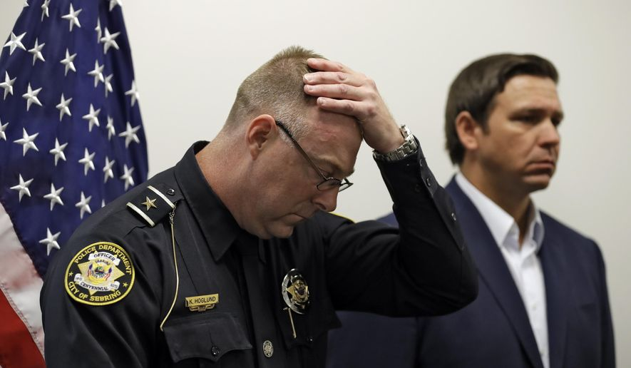 Sebring Police Chief Karl Hoglund wipes his head as he listens to Florida Gov. Ron DeSantis speak during a news conference, Wednesday, Jan. 23, 2019, in Sebring, Fla., after authorities said five people were shot and killed at a SunTrust bank branch. (AP Photo/Chris O'Meara)