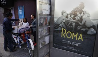 "Women buy pastries and sandwiches from a bicycle vendor in the Roma Sur neighborhood of Mexico City, Wednesday, Dec. 19, 2018, near a newspaper kiosk where Alfonso Cuaron's film ""Roma"" is advertized. News of Alfonso Cuaron's ""Roma"" being nominated for 10 Academy Awards had residents of the director's childhood Mexico City neighborhood joyfully mining their own memories and anticipating showing their children the film someday. (AP Photo/Rebecca Blackwell)"