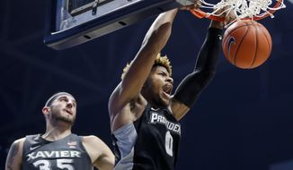 Providence's Nate Watson (0) dunks on Xavier's Zach Hankins (35) in the first half of an NCAA college basketball game, Wednesday, Jan. 23, 2019, in Cincinnati. (AP Photo/John Minchillo)