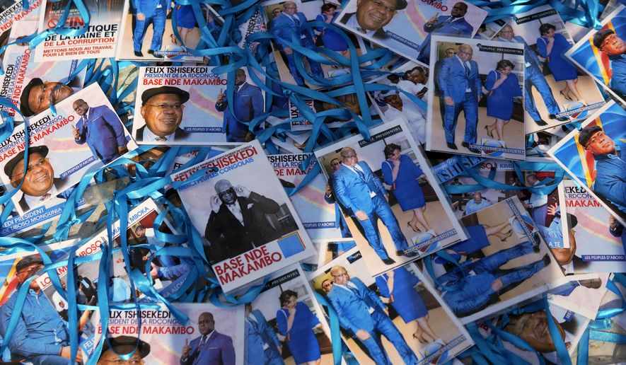 Supporters of Congolese President elect Felix Tshisekedi sell souvenirs outside his party headquarters in Kinshasa, Democratic Republic of the Congo, Wednesday Jan. 23, 2019. Tshisekedi is to be inaugurated Thursday Jan. 24, 2019, having won an election that raised numerous concerns about voting irregularities amongst observers as the country chose a successor to longtime President Joseph Kabila. (AP Photo/Jerome Delay)