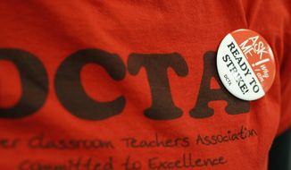 FILE - In this Thursday, Jan. 17, 2019, file photograph, a teacher wears a button on a union shirt in the Denver Classroom Teachers Association, the union's headquarters in south Denver. Teachers voted Tuesday, Jan. 22, 2019, to authorize a strike, which would be the first called in 25 years in the state's largest school district. (AP Photo/David Zalubowski, File)