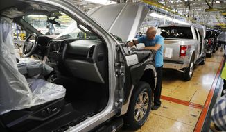 FILE- In this Sept. 27, 2018, file photo a United Auto Workers assemblyman works on a 2018 Ford F-150 truck being assembled at the Ford Rouge assembly plant in Dearborn, Mich. Ford Motor Co. reports financial results Wednesday, Jan. 23, 2019. (AP Photo/Carlos Osorio, File)