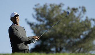 Tiger Woods watches his tee shot on the eighth hole during the pro-am round of the Farmer's Insurance Open golf tournament on the North Course at Torrey Pines Golf Course on Wednesday, Jan. 23, 2019, in San Diego, Calif. (AP Photo/Chris Carlson)
