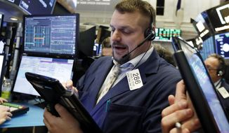 FILE- In this Jan. 18, 2019, file photo trader Michael Milano works on the floor of the New York Stock Exchange. The U.S. stock market opens at 9:30 a.m. EST on Wednesday, Jan. 23. (AP Photo/Richard Drew, File)