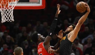 Atlanta Hawks guard Justin Anderson (1) goes up for a dunk as Chicago Bulls forward Bobby Portis (5) defends during the first half of an NBA basketball game Wednesday Jan. 23, 2019, in Chicago. (AP Photo/Matt Marton)