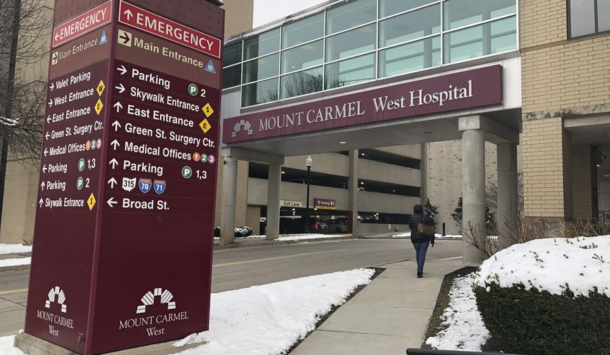 """FILE - In this Jan. 15, 2019 file photo, the main entrance to Mount Carmel West Hospital is shown in Columbus, Ohio. The Columbus-area Mount Carmel Health System said a doctor's orders for potentially fatal doses of pain medicine given to over two dozen patients were carried out by what he calls """"a small number of good people who made poor decisions."""" Mount Carmel Health System said it fired the intensive care doctor, put six pharmacists and 14 nurses on paid leave pending further review and reported its findings to authorities.   (AP Photo/Andrew Welsh Huggins, File)"""