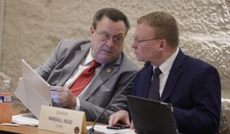 Sen. Michael Young, left, R-Indianapolis, speaks with Sen. Randy Head, R-Logansport, during a committee hearing at the Statehouse, Wednesday, Jan. 23, 2019, Indianapolis. The committee heard testimony on a bill creating a felony charge of fertility fraud for doctors using their own sperm or eggs without the patient's consent. (AP Photo/Darron Cummings)