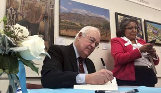 """Former independent counsel Kenneth Starr signs a copy of his recent book """"Contempt: A Memoir of the Clinton Investigation"""" at the University of New Mexico School of Law in Albuquerque, N.M., Wednesday, Jan. 23, 2019. Starr, who investigated President Bill Clinton, says he wants the public to trust the checks and balances in the system established to hold presidents accountable. (AP Photo/Mary Hudetz)."""
