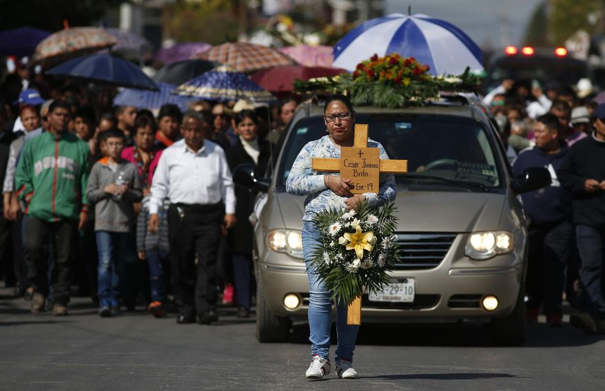 A woman carries a cross with the name Cesar Jimenez Brito during his funeral procession after he died when a gas pipeline exploded in the village of Tlahuelilpan, Mexico, Sunday Jan. 20, 2019. A massive fireball that engulfed locals scooping up fuel spilling from a pipeline ruptured by thieves in central Mexico killed dozens of people and badly burned dozens more on Jan. 18. (AP Photo/Claudio Cruz)