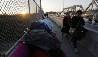 In this Thursday, Jan. 10, 2019, photo pedestrians pass a makeshift encampment where migrants seeking asylum wait in Matamoros, Mexico, on a bridge connecting the U.S. and Mexico. The latest proposal President Donald Trump and Senate Republicans made to fund the border wall includes provisions that would be far more consequential than the wall, by making the already difficult task of winning asylum even harder. (AP Photo/Eric Gay)