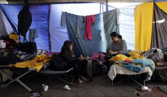 In this Thursday, Jan. 10, 2019, photo, Clarisa Landaverry, right, talks with her daughter, 9-year-old Monica, inside the encampment for asylum seekers waiting to cross the nearby U.S.-Mexico bridge, in Matamoros, Mexico. Asylum seekers at the border sometimes wait weeks or months to enter the U.S. for processing. (AP Photo/Eric Gay)