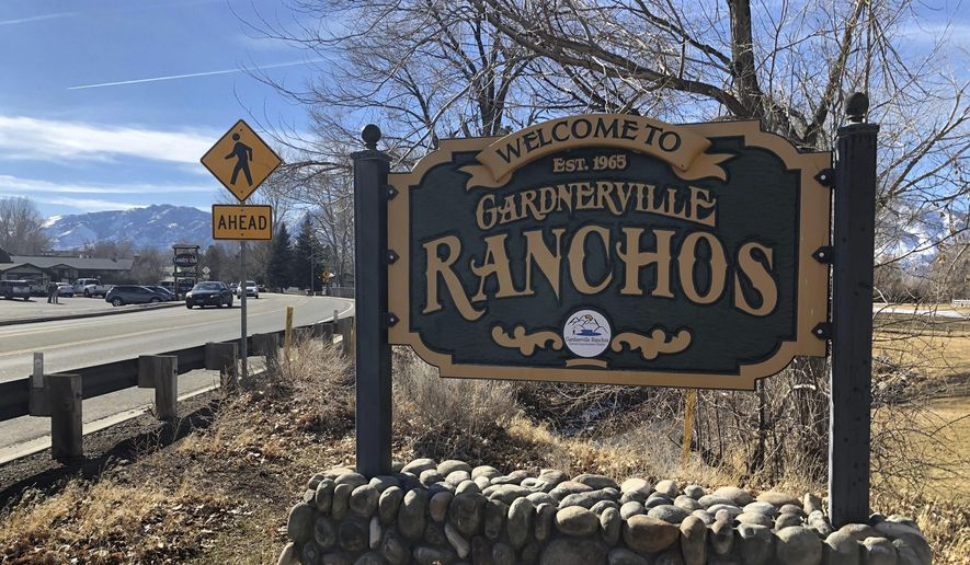 A welcome sign sits at the entrance to the tight tight-knit community of Gardnerville Ranchos, Nev., Wednesday, Jan. 23, 2019, where two women were recently found dead in their homes. The killings of the two women and a couple up north in Reno that police say were committed by a man in the U.S. illegally have put the community on edge. (AP Photo/Michelle L. Price)